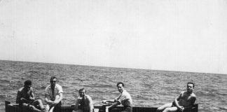 1956. Grup de amics de Can Tunis, donant un fen un tom per la platja en xalana. Proc. Julio Baños