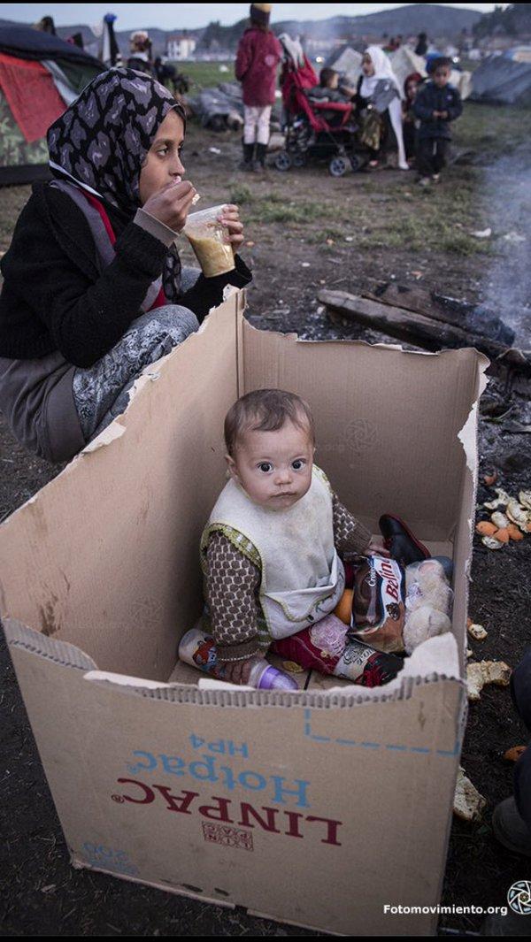 Una mare amb el seu fill sopen fora del campament d'Idomeni